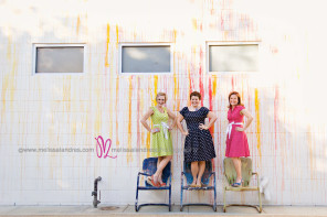 Fun photos of 3 ladies in vintage inspired ModCloth dresses in front of paint splattered wall by family photographer Melissa Landres